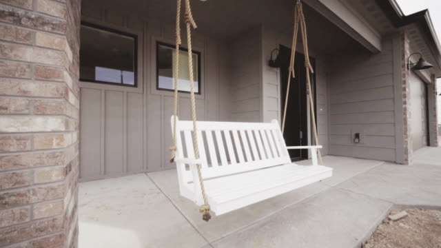 Classic White Front Porch Swing at a New Custom Home Classic White Front Porch Swing at a New Custom Home porch stock videos & royalty-free footage