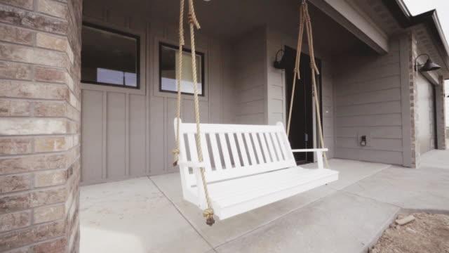 classic white front porch swing at a new custom home - portico video stock e b–roll