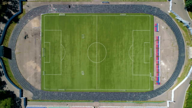 Classical empty old stadium from birds eye view Drone view. Green Football soccer field. Aerial view of the empty old stadium. Green Football soccer field. Drone footage. Angarsk city, Siberia, Russia top garment stock videos & royalty-free footage
