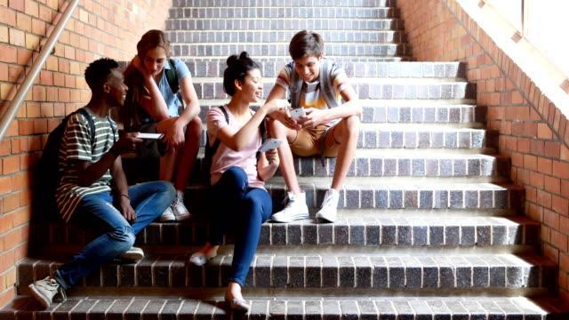 Klassenkameraden sitzen auf der Treppe und benutzen Handy – Video