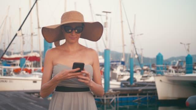 vídeos de stock, filmes e b-roll de senhora elegante no vestido usando seu smartphone que anda no cais do porto com os iate no fundo - marina