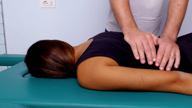 vídeos de stock e filmes b-roll de clavicle massage: physiotherapist massaging the patient's clavicle - massajar