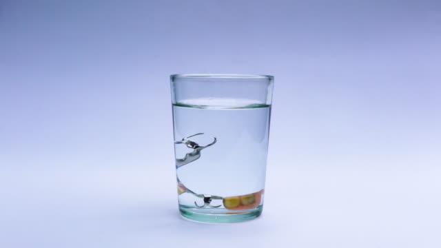 將片劑放入裝滿淡水的玻璃杯中,對假牙進行清潔和消毒 - 部分 個影片檔及 b 捲影像