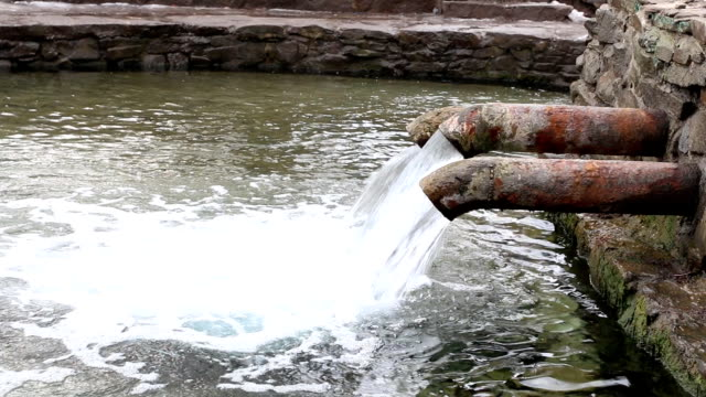 Clean drinking water flowing from a old metal pipe. video