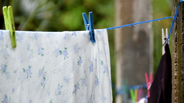 Clean laundry drying on the washing line in the rain.