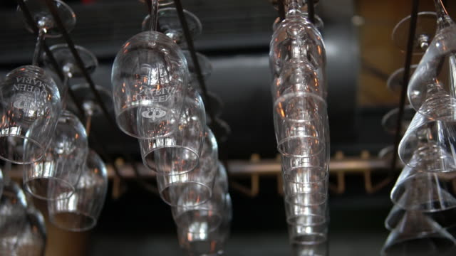 Clean washed and polished glasses hanging over a bar rack
