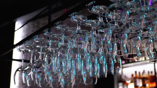 rena vinglas hänger upp och ner ovanför en bar rack i restaurangen - pub bildbanksvideor och videomaterial från bakom kulisserna