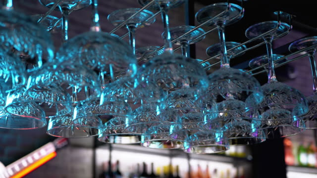 Clean Wine Glasses Hanging Upside Down above a Bar Rack in Restaurant