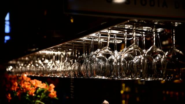 Clean wine glasses hanging upside down above a bar rack in restaurant. Bartender wipes glasses