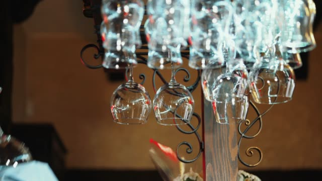 Clean wine glasses hanging upside down above a bar rack in restaurant.