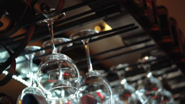 Clean wine glasses prepared by bartender and hung on the bar at a restaurant or cafe.
