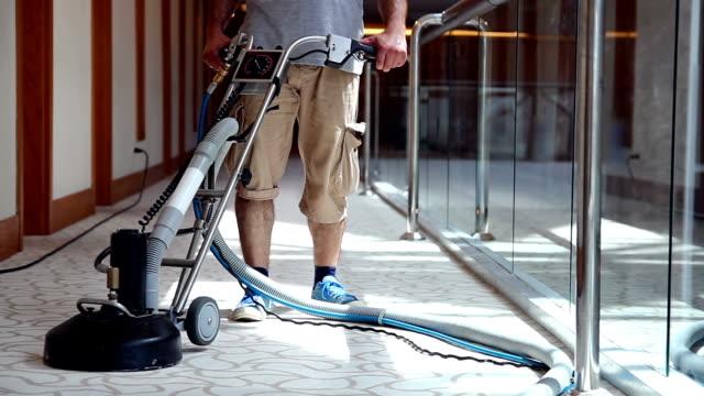 operaio pulizia maschile tappeto pulizia corridoio hotel - moquette video stock e b–roll