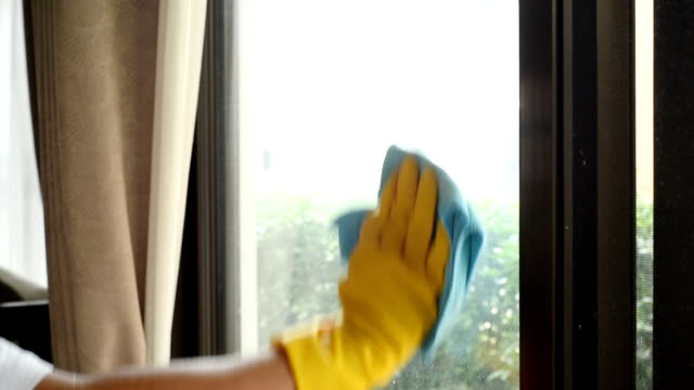 cleaner spraying on window glasses and wiping off by microfiber cloth , cleaning footage concept - disinfectant stock videos & royalty-free footage