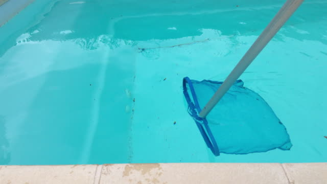 cleaning a domestic outdoor pool with net - addetto alle pulizie video stock e b–roll