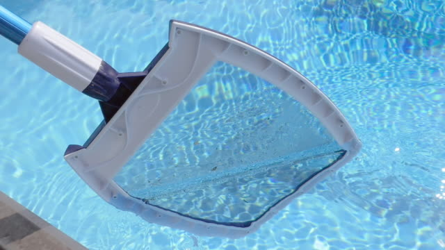 Cleaning a Swimming Pool with a Skimmer Net in Slow Motion Cleaning a public swimming pool with a mesh skimmer in slow motion. The long handled net cleans leaves and twigs off surface of the sparkling water. Closeup of the skimmer can be used for professional pool and spa cleaner commercials. chlorine stock videos & royalty-free footage