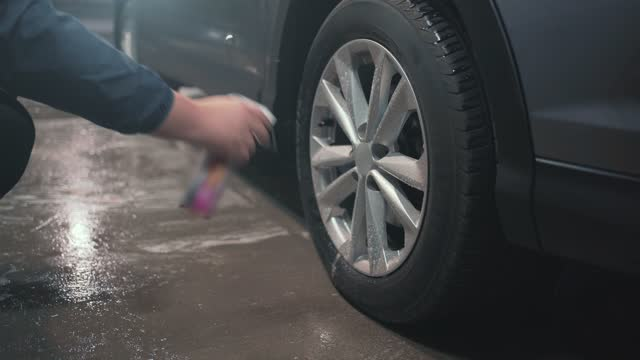 Cleaning aluminium wheels with special spray cleaner, close up. Car wash and care video