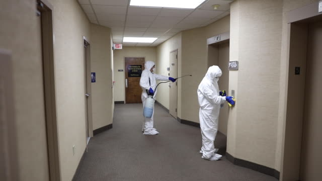 Cleaning And Disinfecting Office Two people in protective workwear cleaning and disinfecting offices. cleaning stock videos & royalty-free footage