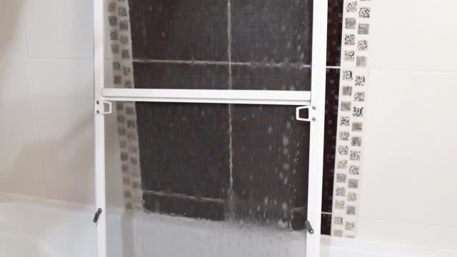 reinigung und waschen staubigen moskitonetz-bildschirm für fenster. hausarbeitskonzept - moskitonetz stock-videos und b-roll-filmmaterial