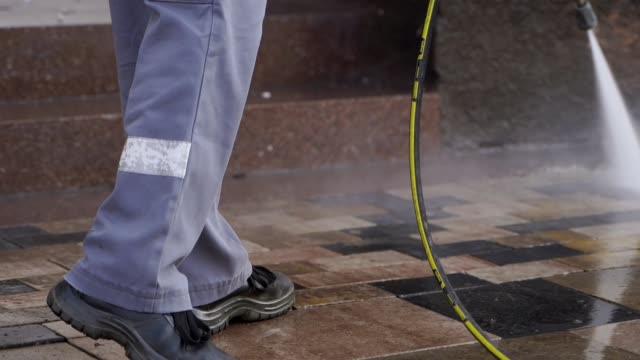 Cleaning city streets with water pressure washer. Janitor sprays city street sidewalk paving slabs. Worker disinfects floor and surfaces from coronavirus. Antibacterial sanitary measures on quarantine