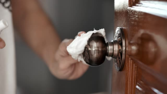 covid-19 : pulizia della maniglia della porta - pulito video stock e b–roll