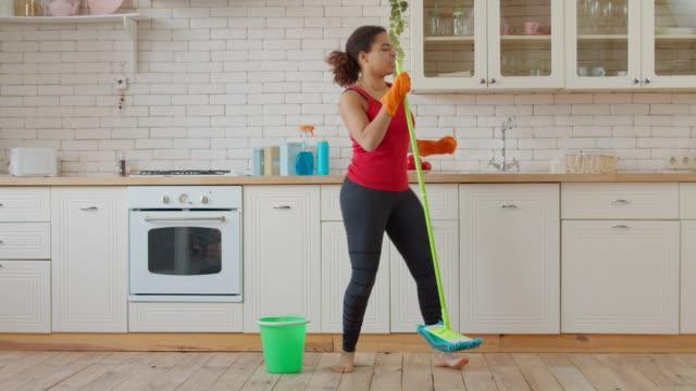 pulizia eccitata donna africana che balla con mop - pulito video stock e b–roll