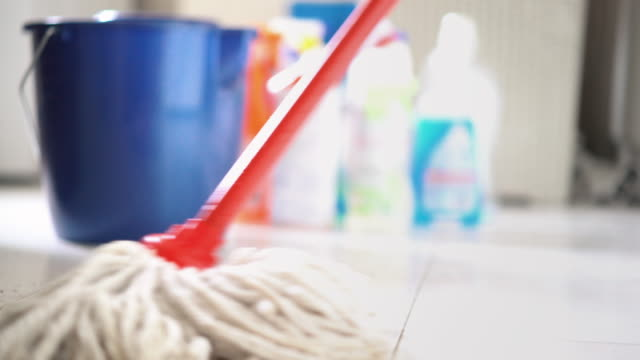 Cleaning floors. Closeup low angle view of unrecognizable person cleaning tiled floor with a mop. Blue plastic bucket and a lot of cleaning products in background. 4k video cleaning stock videos & royalty-free footage