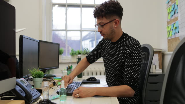 rengöring hans arbetsstation - endast en man i 30 årsåldern bildbanksvideor och videomaterial från bakom kulisserna