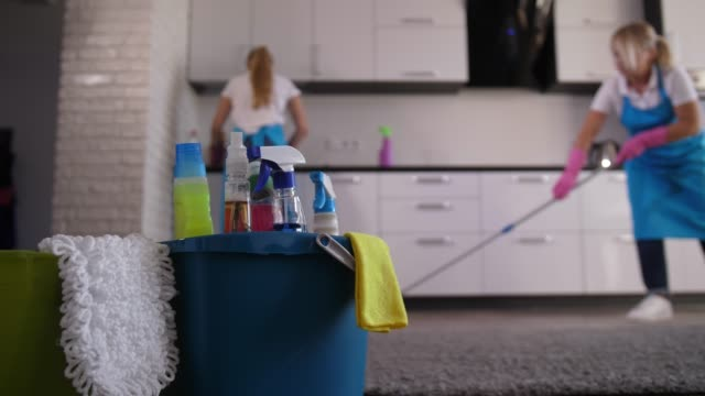 Cleaning ladies working in house kitchen Two female janitors in aprons and gloves wiping kitchen surface and mopping, close-up on cleaning tools and detergents. Professional cleaners washing kitchen area during house clean up service stock videos & royalty-free footage