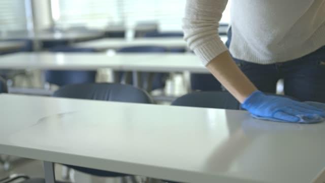 la donna delle pulizie disinfetta i tavoli in un'aula scolastica durante il periodo di quarantena - pulito video stock e b–roll