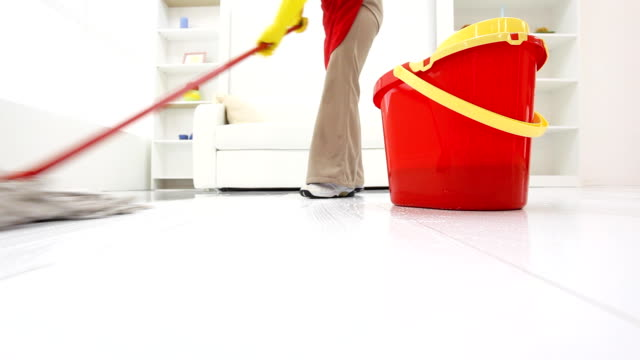 Cleaning lady mopping floors in a room. video