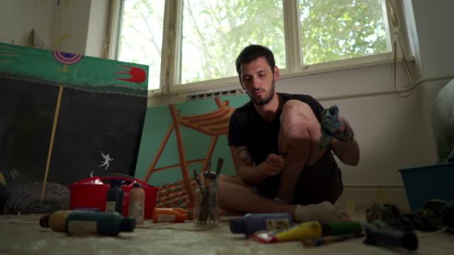 vidéos et rushes de nettoyage des pinceaux après la classe d'art - pots de bureau