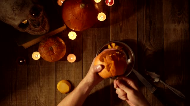cleaning pumpkin lantern from innards and seeds for halloween decorations - zucca legenaria video stock e b–roll