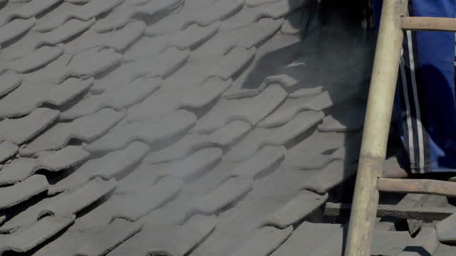 Cleaning roof tile from volcanic ash after eruption, Indonesia video