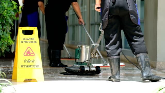 Équipe de service nettoyage sol avec machine de lavage et le nettoyage dans l'étiquette de la processus - Vidéo