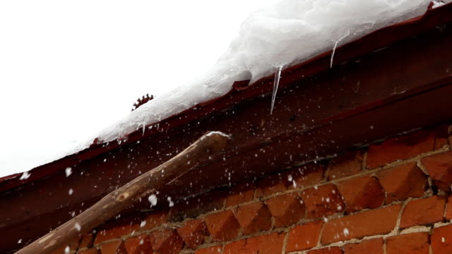 Cleaning snow and ice from roof cornice - countryside house video
