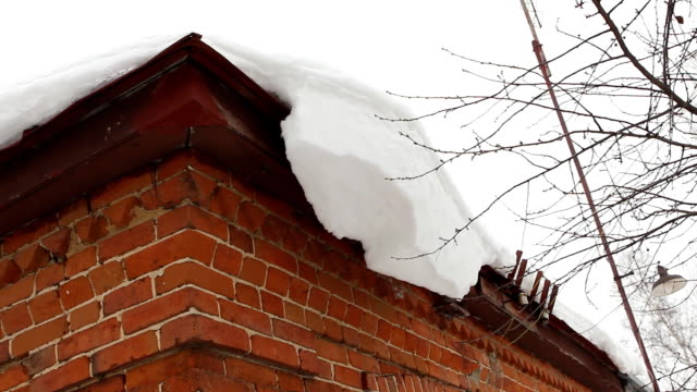 Cleaning snow from roof eaves cornice - countryside house video