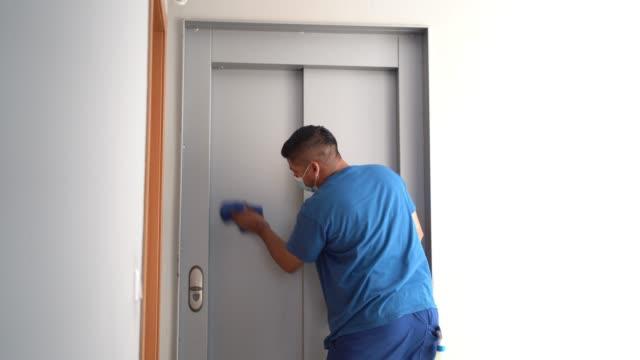 vídeos y material grabado en eventos de stock de personal de limpieza desinfectando la puerta del ascensor para evitar la propagación de covid19 - brigada