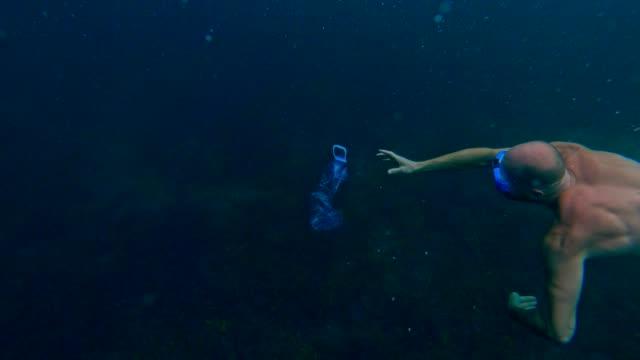 Nettoyage de l'océan. Homme, attraper la bouteille d'animal familier sous la surface de la mer - Vidéo