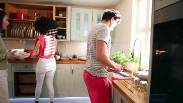 Cleaning Up as a Team! A shot of a group of friends working in the kitchen, one man is washing the dishes and two women are tidying up. washing dishes stock videos & royalty-free footage