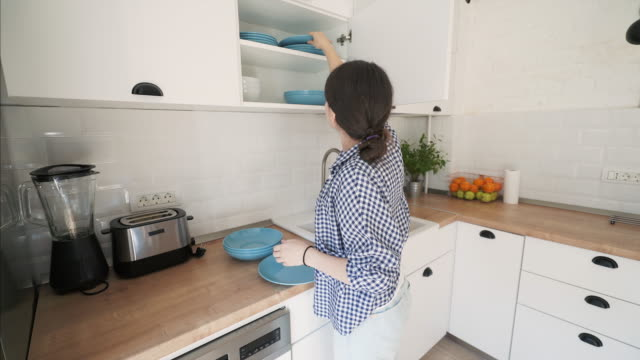 Cleaning up in the kitchen. Cleaning up in the kitchen. Stay at home young woman putting clean dishes in the cabinet. order stock videos & royalty-free footage