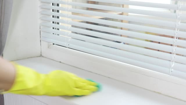 cleaning washing window sill with a sanitary spray and a sponge by a woman's hand in yellow rubber glove - lysol stock videos & royalty-free footage