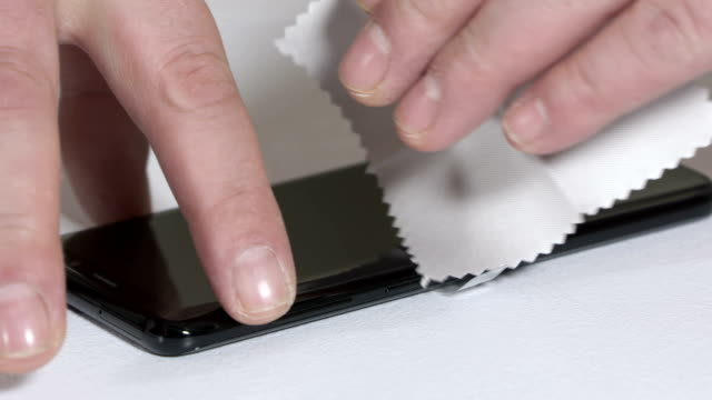 Cleaning with microfiber cloth a touch screen on new mobile phone video