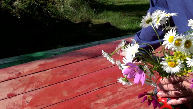 cleaning wooden table  and put vase with flowers video