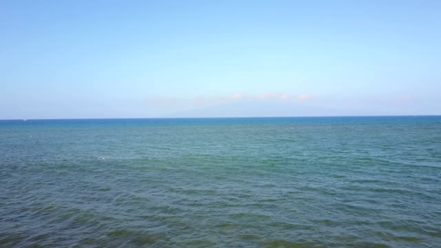 vídeos de stock, filmes e b-roll de clear blue sky over calmo oceano costa de maui - largo descrição geral