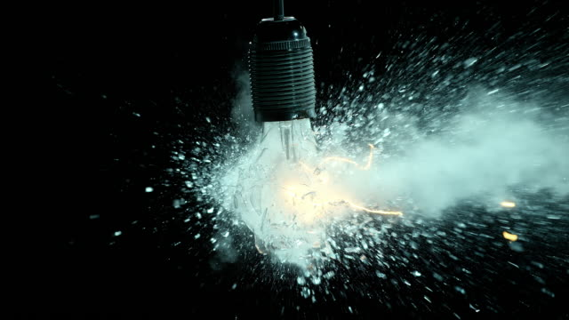 SLO MO clear lit light bulb explosion Slow motion medium locked down shot of a lit suspended clear light bulb exploding into tiny pieces on black background. breaking stock videos & royalty-free footage