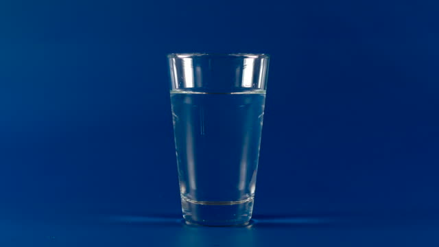 Clear water drinks from a glass cup on a blue background - Stop motion video
