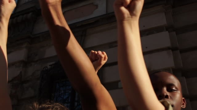 clenched fists raised in the air. violence protests, , people chanting stop racism slogans, interracial group of people - pugno video stock e b–roll
