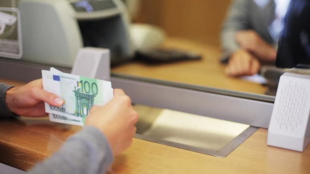 clerk counting money and customer at bank office - valuta dell'unione europea video stock e b–roll