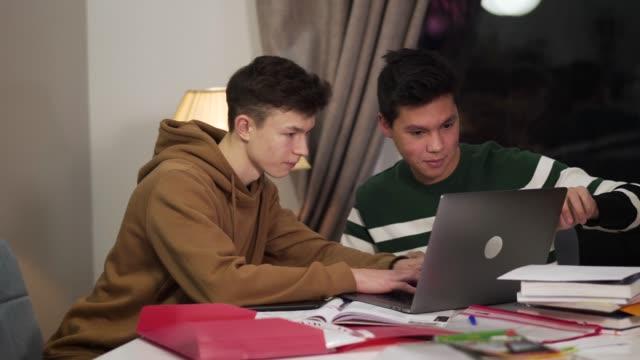 intelligente ragazzo caucasico che aiuta il suo amico asiatico a trattare con il laptop. amichevoli compagni di gruppo multirazziali che studiano al chiuso la sera. istruzione, intelligenza, stile di vita. - solo bambini maschi video stock e b–roll