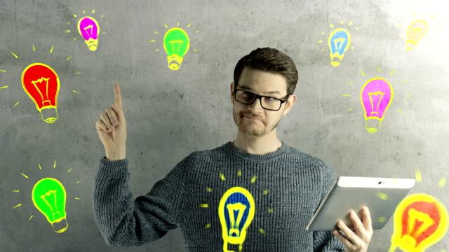 Clever hipster creative man think touch digital tablet ipad gets an idea, which jumps up as symbolic colored cartoon animation shape lamps around him on natural background video